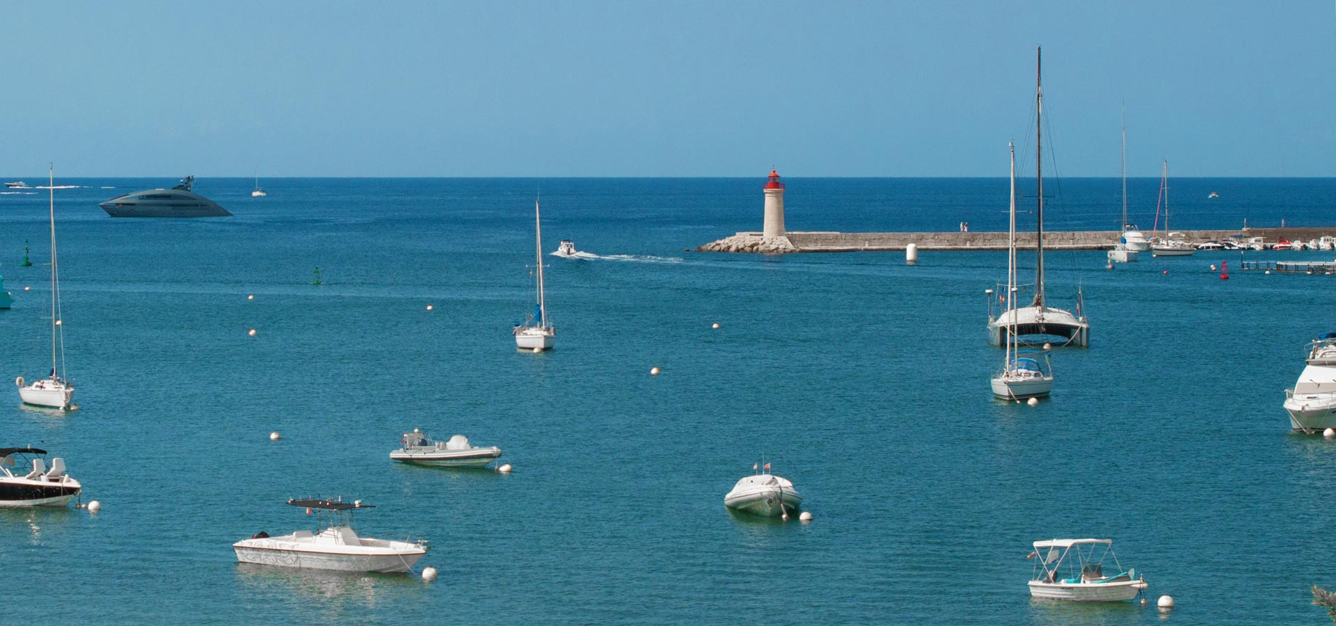 View from a roof terrace of a penthouse in Port Andratx. View over a lighthouse, yacht and boat anchorage, harbour and marina La Vela