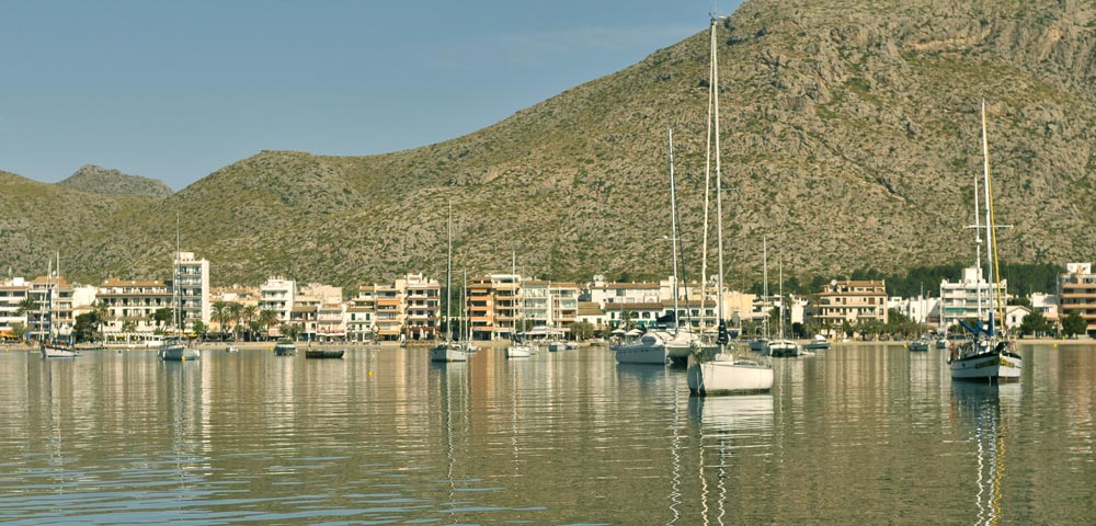 Port Puerto Pollensa Pollenca anchorage boats view harbour sea still water sailing yachts houses real estate Mallorca spain neighbourhood guides casafari