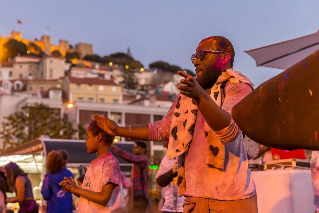 man dancing during the holi festival with Martim Moniz property in the background.
