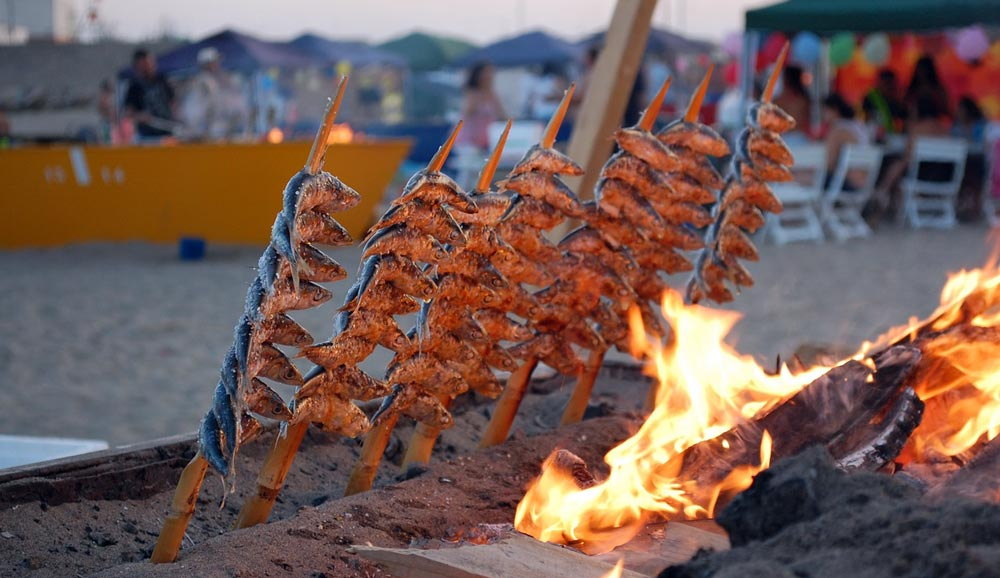 Typical atmosphere on the evening beach grilling freshly caught fish. Delicious local food is praised by Malaga property buyers.